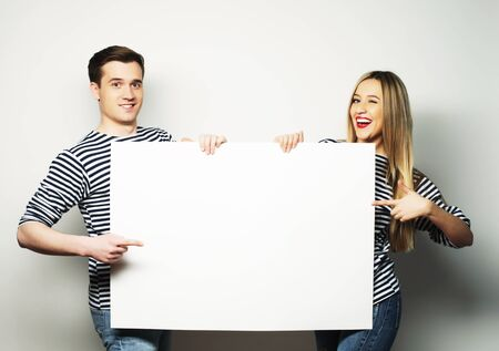 lovely couple: Lovely couple holding a banner -  over a gray background Stock Photo