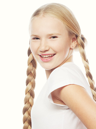 12 13: Portrait of a beautiful European blonde girl with braids. Smiling girl. Studio shot, isolated on white background. Stock Photo