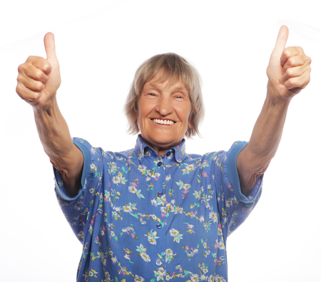 80 year old: Old happy woman showing ok sign on a white background