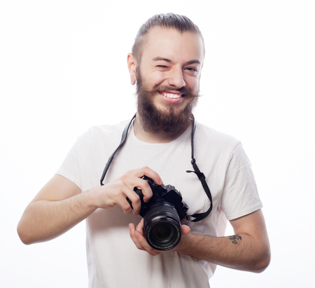 tehnology: life style, tehnology and travel concept: bearded man wearing white t-shirt with a digital camera isolated on a white background
