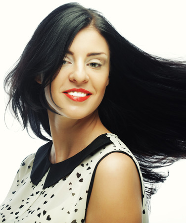 dishevel: Young happy woman with wind in hair. Studio shot. Stock Photo