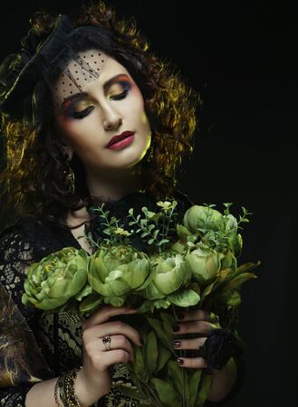 brigt: Young curly woman with brigt visage holding big green flowers Stock Photo