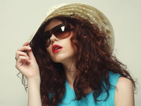 Beautiful young surprised woman wearing hat and sunglasses photo