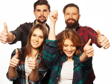 university admission: life style, education and people concept:  happy team of students showing thumbs up. Studio shot over white background. Hipster style. Special toning. Stock Photo