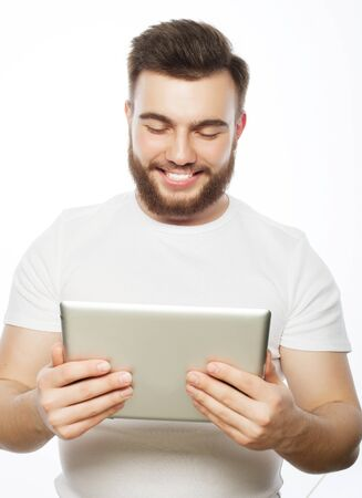 tehnology: Tehnology and lifestyle concept: young man wearing white t-shirt using a tablet computer - isolated over a white background