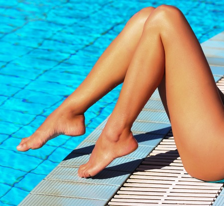 legs: Sexy female legs at blue water of swimming pool