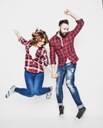 making fun: life style, happiness and people concept: Happy loving couple. Jumping over light grey background. Special Fashionable toning. Stock Photo
