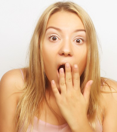 woman mouth open: Close-up portrait of surprised blond girl holding her head in amazement and open-mouthed. Stock Photo