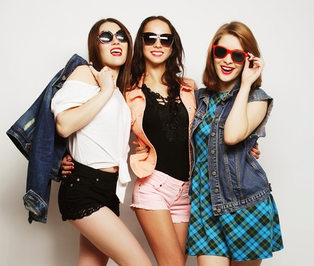 Fashion portrait of three stylish sexy hipster girls best friends, over gray background. Happy time for fun. 版權商用圖片