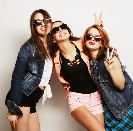 Fashion portret van drie stijlvolle sexy hipster meisjes beste vrienden, over grijze achtergrond. Gelukkige tijd voor de lol.