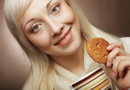 young blond woman with coffee and cookies photo