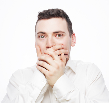 life style  and people concept: Shocked young man  covering mouth with hands and looking at camera while standing against white background photo