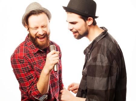Hipsters: twee jonge mens zingen met microfoon. Geïsoleerd op wit. Stockfoto