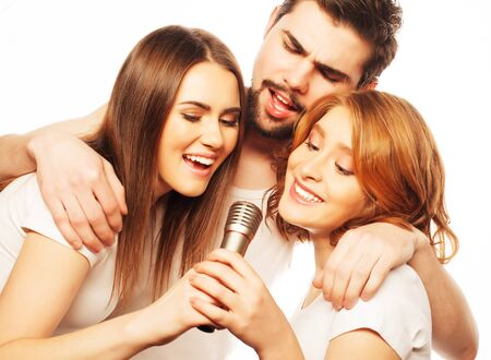 karaoke singer: People, friendship  and leisure concept: group of young happy friends  having fun at karaoke, hipster style.Isolated on white. Stock Photo