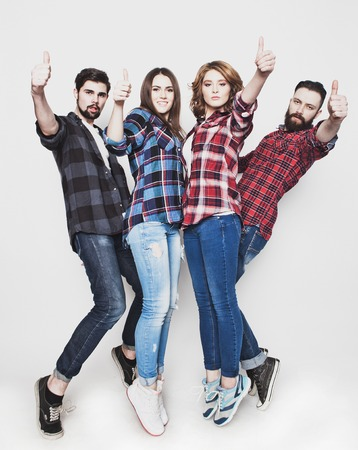 life style, education and people concept:  happy team of students showing thumbs up. Studio shot over white background. Hipster style. Special toning. Stock Photo