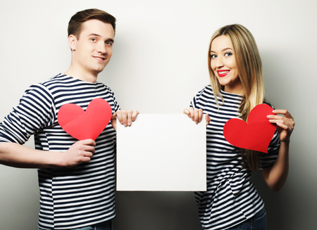 flirtation: couple, love and family concept: happy couple holding white blank and red hearts.