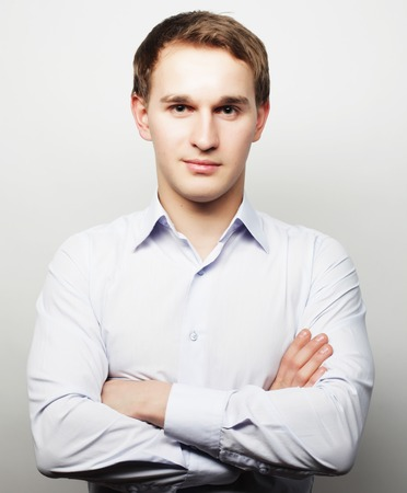 business, successful and people concept - Handsome young business man in white shirt looking at camera standing against grey  background