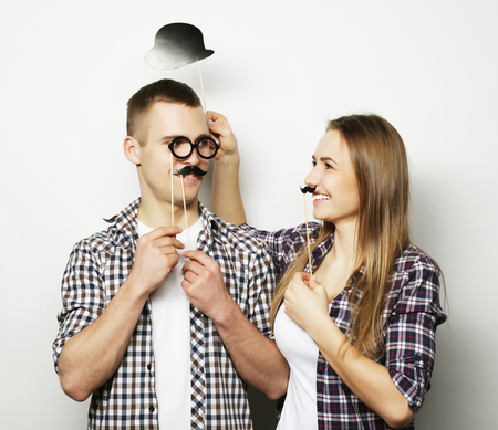 mustaches: people, party, love and leisure concept - lovely couple holding party glasses and mustaches on sticks, over white  background