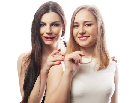 white girl: Two young girl friends standing together and looking at camera. Over white background.