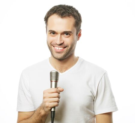 leasure: Life style, people and leasure concept: a young man wearing a white shirt holding a microphone and singing. Isolated on white.