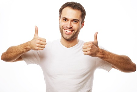 life style  and people concept: Happy handsome man wearing white t-shirt showing thumbs up over isolated background Stockfoto