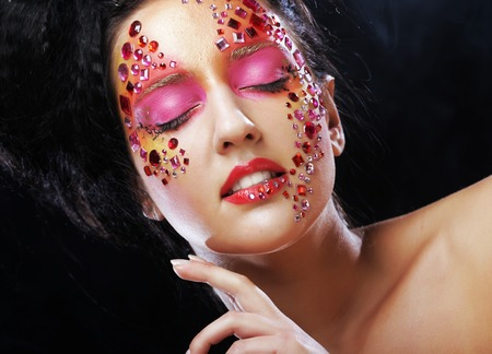 eye closed: Closeup beauty portrait of attractive model face with bright rhinestones visage.Woman with eye closed. Stock Photo