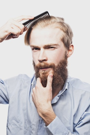guy standing: young bearded man combing his hair and looking at camera while standing against light grey background