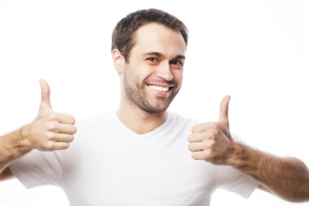 adult boys: life style  and people concept: Happy handsome man wearing white t-shirt showing thumbs up over isolated background Stock Photo