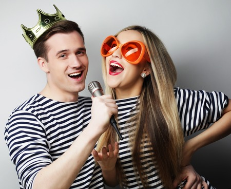 people, friendship, love and leisure concept - beautiful young loving couple with microphone. Big orange glasses and crown. Ready for party. Standard-Bild