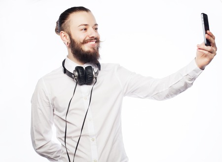 tehnology: Internet, tehnology and people concept: a young man with a beard in shirt holding mobile phone and making photo of himself while standing against white  background.