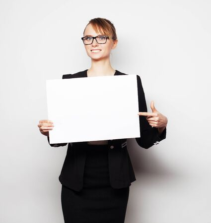 add text: Business, finance and people concept: Portrait of a beautiful business woman holding a blank billboard. Ready to add text. Over grey  background.