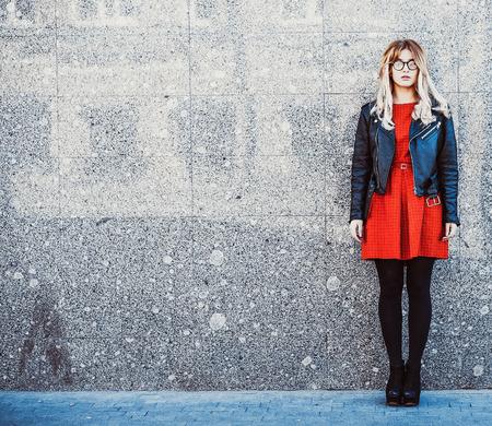 Fashion portret van hipster vrouw in een stijlvolle zomer casual outfit poseren tegen muur achtergrond.