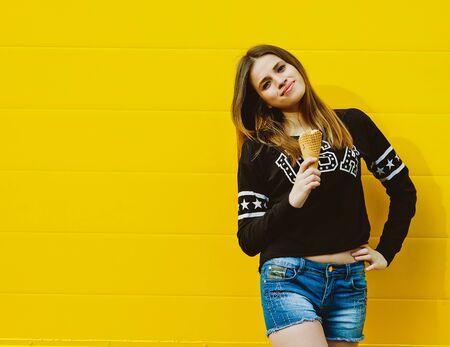comiendo helado: Retrato de la moda al aire libre de la chica joven inconformista con helado sobre fondo de pared de color amarillo Foto de archivo