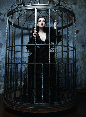 gothic girl: Fashion model in fantasy dress posing in steel cage.