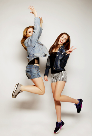 naughty: lifestyle portrait of two young hipster girls best friends jump over gray background Stock Photo