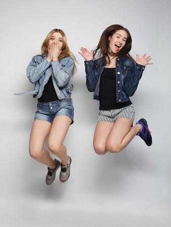 mujeres fashion: estilo de vida retrato de dos chicas jóvenes inconformista mejores amigos saltar sobre fondo gris Foto de archivo
