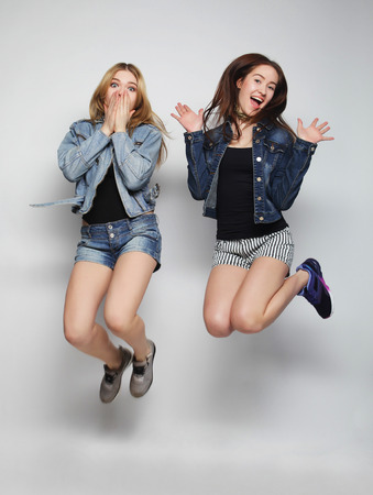 lifestyle portrait of two young hipster girls best friends jump over gray background Standard-Bild