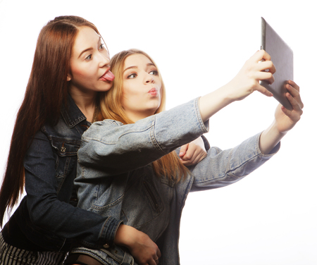 friendliness: Dos mujeres bastante jovenes que toman un autorretrato con una tableta, aislado en blanco Foto de archivo