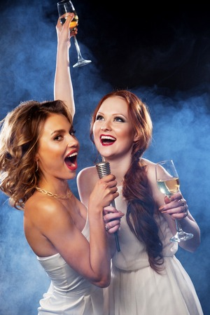 karaoke singer: Karaoke party. Beauty girls with a microphone singing and dancing over dark background.