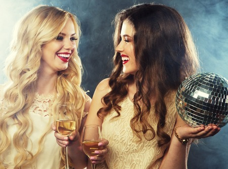 two beautiful young women with wine glasses and disco ball. 免版税图像