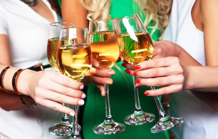 girls: Group of partying girls clinking flutes with sparkling wine, close up