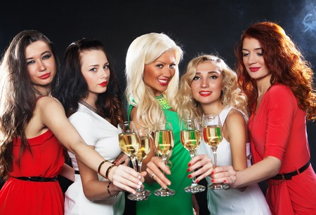 partying: Group of partying girls clinking flutes with sparkling wine