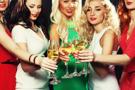 clinking: Group of partying girls clinking flutes with sparkling wine, close up