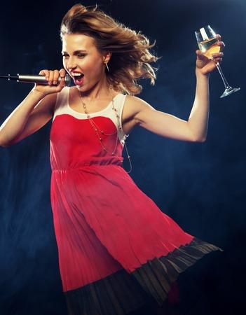 cantando: Niña feliz joven que canta en el micrófono en la fiesta