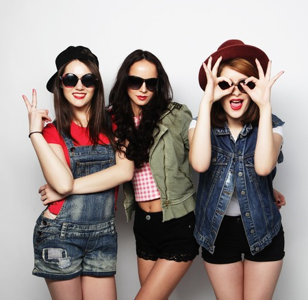 denim jeans: Three stylish sexy hipster girls best friends.Standing together and having fun. Looking at camera. Over gray background. Stock Photo
