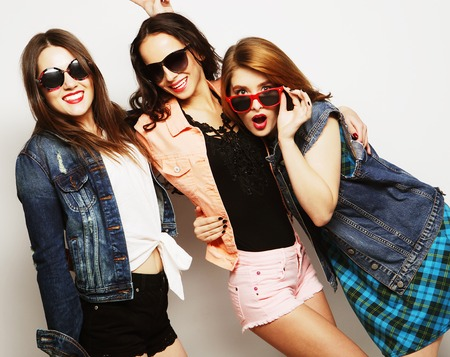 Fashion portrait of three stylish sexy hipster girls best friends, over gray background. Happy time for fun. 免版税图像
