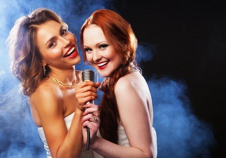 cantando: Fiesta de karaoke. Muchachas de la belleza con un micrófono cantando y bailando sobre fondo oscuro.