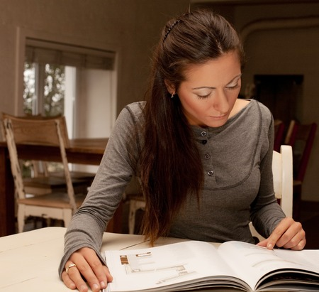 home  concept - smiling young  woman reading magazine at home Stock Photo