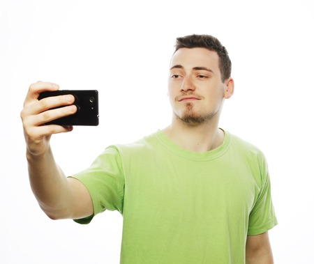tehnology: Life style, tehnology and people concept: a young man in shirt holding mobile phone and making photo of himself while standing against white background.