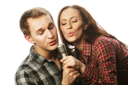 karaoke singer: Karaoke - Lovely couple with microphone. Young and beauty. Hipster style. Over white background.